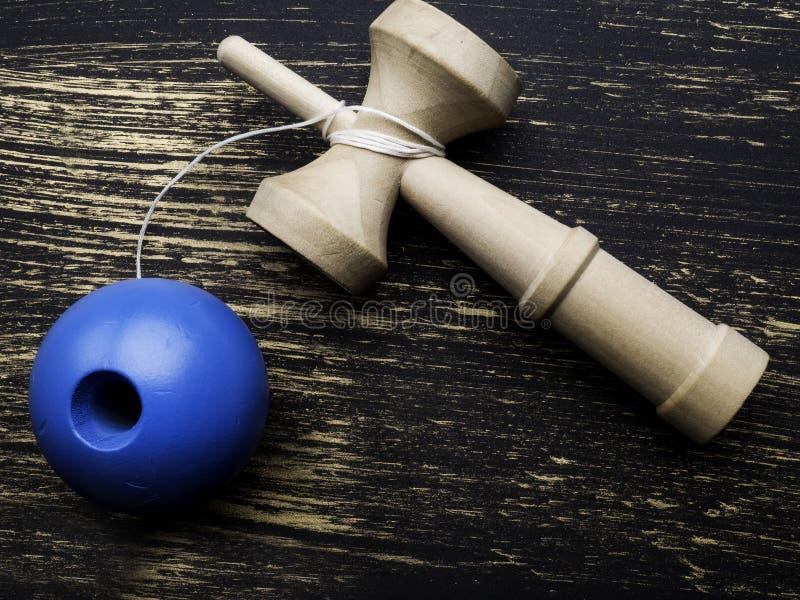 El juguete japonés tradicional Kendama en fondo oscuro, se cierra encima del juguete de madera de Japón foto de archivo