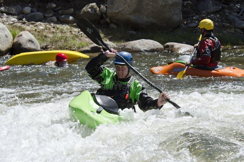 El Kayaker maniobra el kajak en el Rapid de Whitewater imagenes de archivo