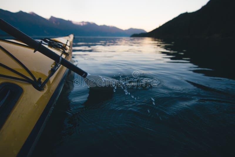 El Kayaking solamente en el agua tranquila con las montañas en el fondo mientras que puesta del sol foto de archivo libre de regalías