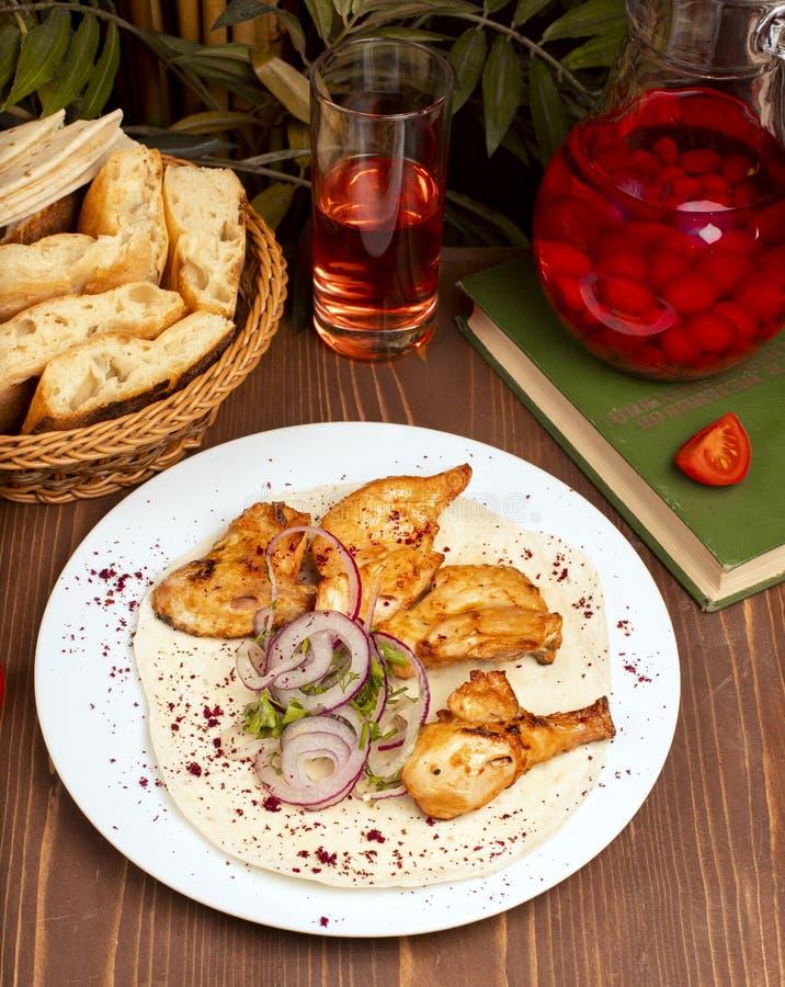 El kebab asado a la parrilla de las alas de pollo sirvió con composto imagen de archivo