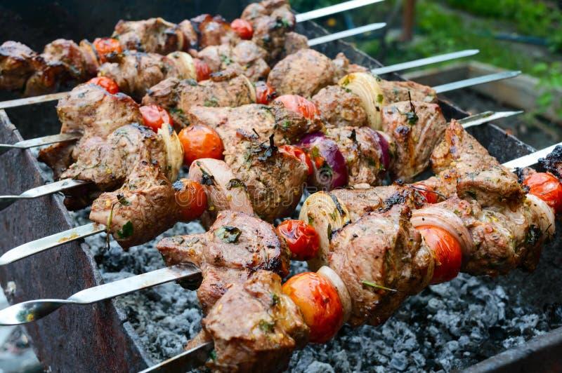 El kebab jugoso del cerdo, tomates en los pinchos, frió en un fuego al aire libre imagenes de archivo