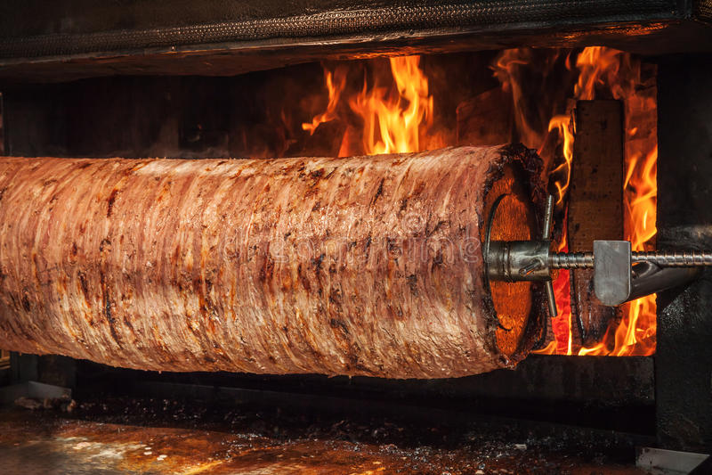 El kebab turco del doner se está preparando en un horno con el fuego abierto imagen de archivo libre de regalías