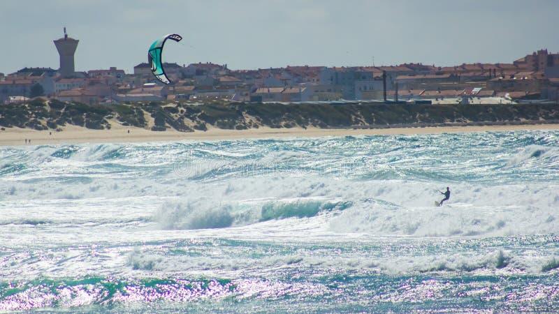 El kitesurfing de entrenamiento en las aguas que apresuran de la playa de Baleal, Portugal foto de archivo