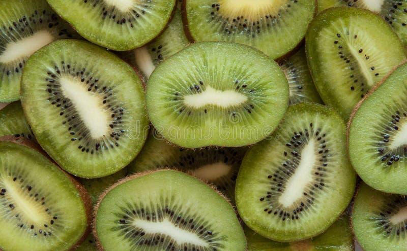 El kiwi cortó el fondo verde Porciones de frutas tropicales verdes Corte el kiwi en pedazos fotos de archivo libres de regalías