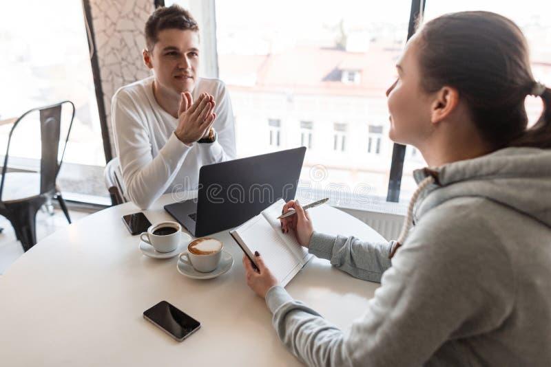 El líder acertado joven hermoso en la camisa blanca habla de la compañía y de las sonrisas en una mujer joven durante una entrevi foto de archivo
