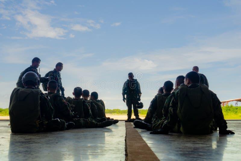 El líder de equipo del paracaídas informa a sus tropas equipadas engranaje lleno en el hangar del aeroplano fotos de archivo libres de regalías