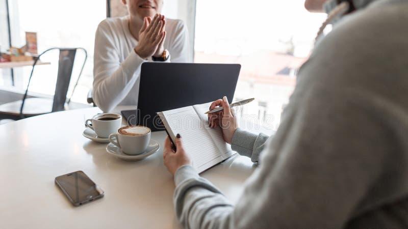 El líder del hombre que se sienta con un ordenador portátil dice a un colega sobre los logros de la compañía en un café Primer de imagen de archivo libre de regalías