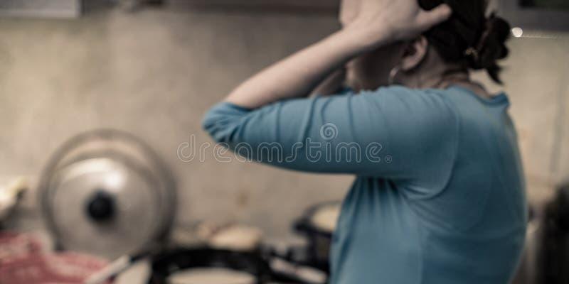 El lío en la cocina una mujer lleva a cabo su cabeza en horror del caos fotografía de archivo