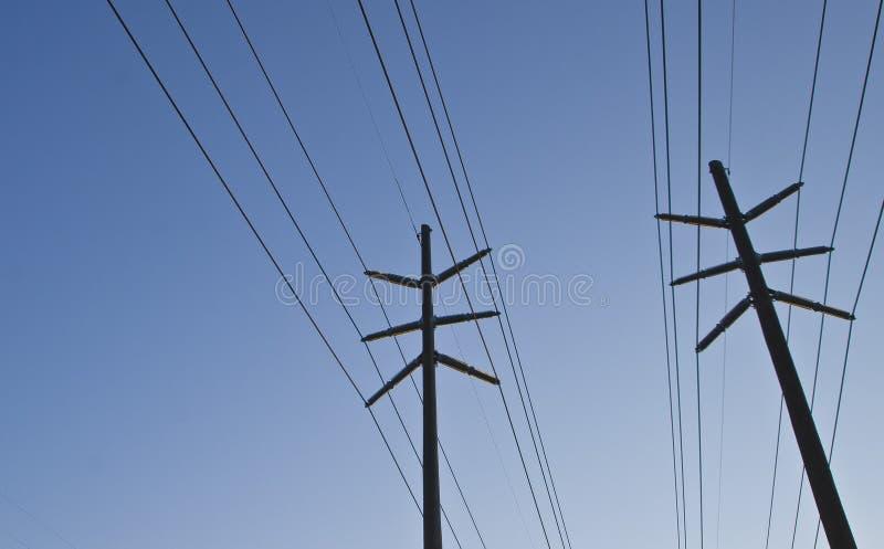El lado de las líneas eléctricas en el cielo azul imagenes de archivo