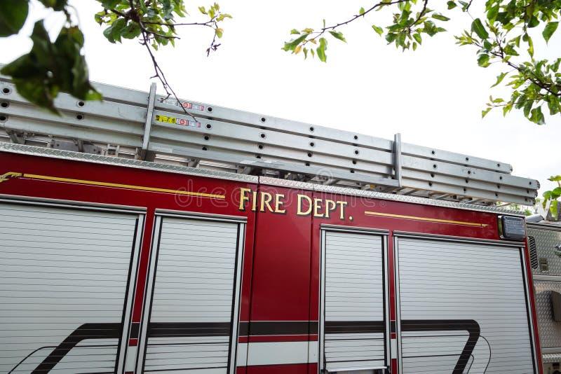 El lado de un coche de bomberos rojo con el cuerpo de bomberos escrito en el lado foto de archivo libre de regalías