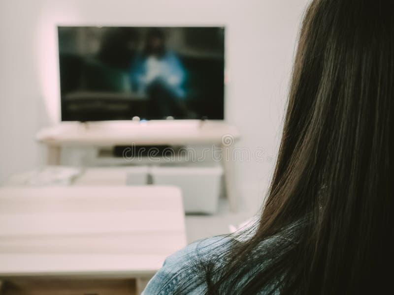 El lado trasero de la mujer del pelo negro sienta, relaja y ve la TV en su liv fotos de archivo libres de regalías