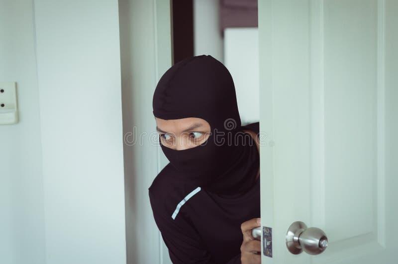 El ladrón del hombre en máscara negra abre la puerta que roba algo de casa fotografía de archivo libre de regalías