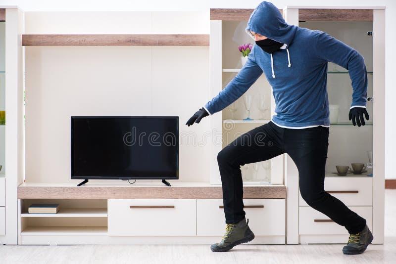 El ladrón del hombre que roba el aparato de TV de la casa fotos de archivo libres de regalías