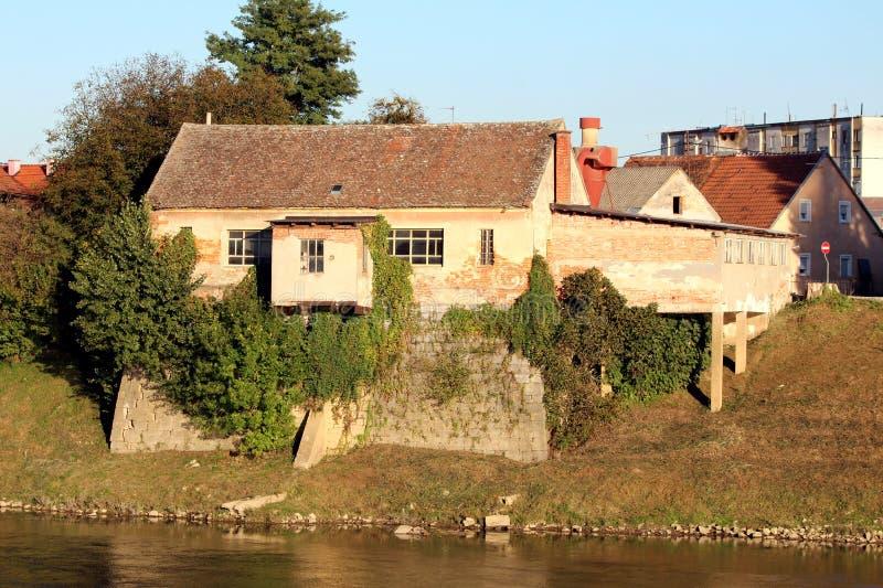 El ladrillo rojo dilapidó casa parcialmente demasiado grande para su edad abandonada de la familia grande empleada la fundación d fotos de archivo