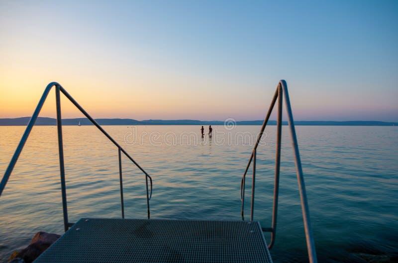 El lago Balatón en la puesta del sol con los bañistas y escaleras al agua imagenes de archivo