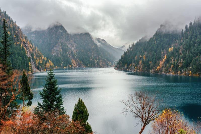 El lago largo entre las montañas enselvadas de la caída en la niebla, Jiuzhaigou fotografía de archivo