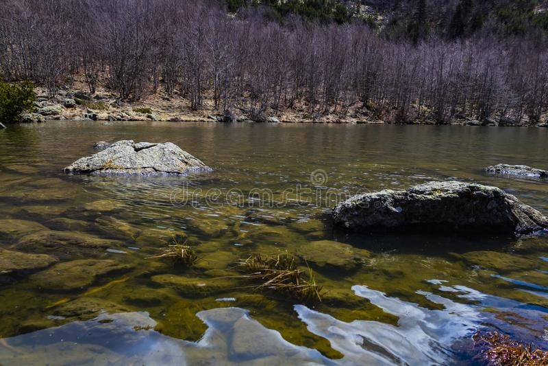 El lago, las rocas y un día de primavera imagen de archivo
