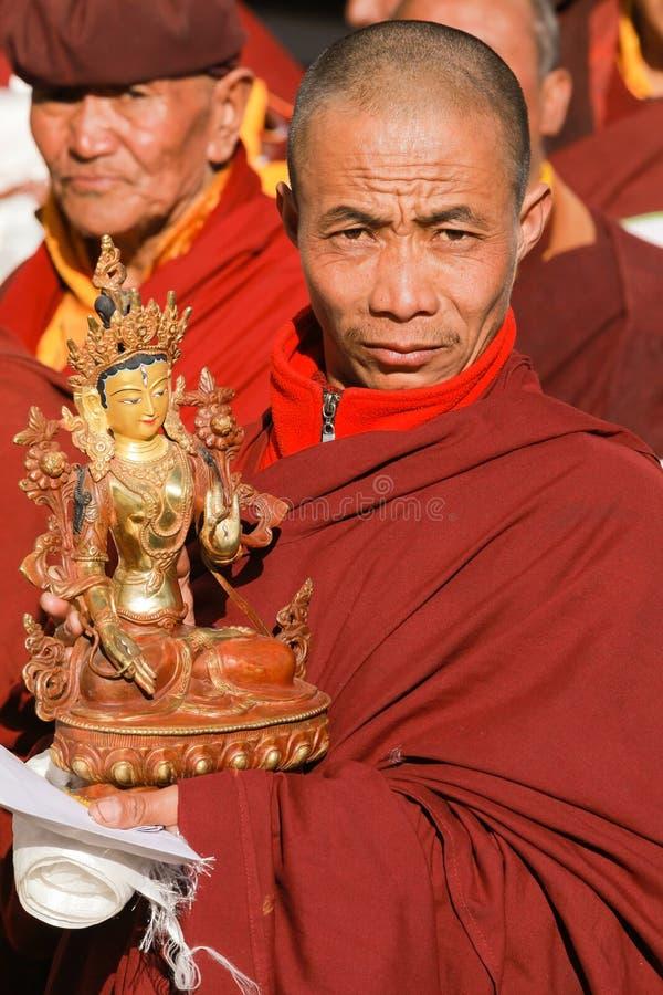 El lama budista lleva la estatua del Bodhisattva durante ceremonia religiosa foto de archivo