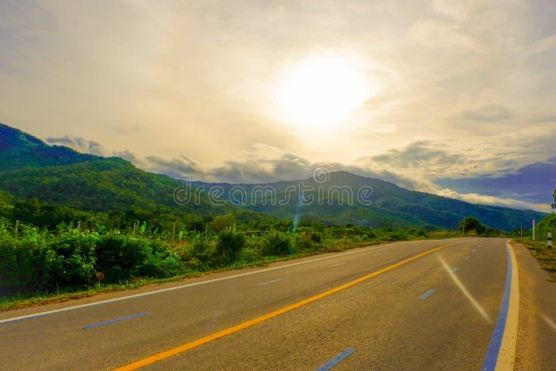 El largo camino pasa a través de las montañas y del cielo azul el día de fiesta imagen de archivo libre de regalías