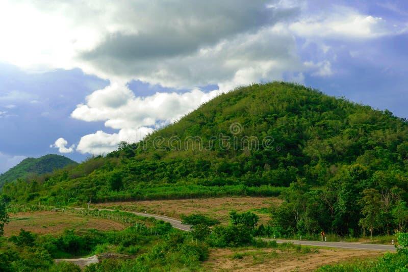 El largo camino pasa a través de las montañas y del cielo azul el día de fiesta imágenes de archivo libres de regalías