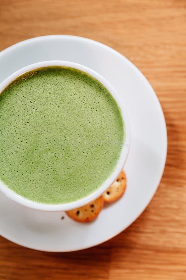 El latte caliente y liso del té verde con espuma sirvió en la taza de cerámica blanca con las galletas fotos de archivo libres de regalías