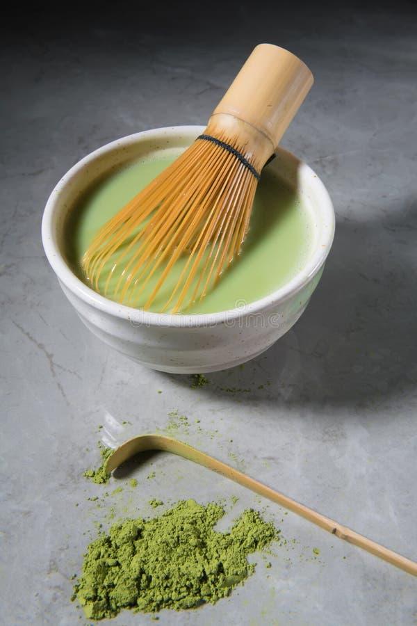 El latte del matcha del té verde con el bambú chasen y la cuchara de bambú en un cuenco en el mármol gris Concepto japon?s de la  foto de archivo libre de regalías