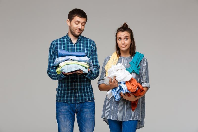 El lavado hermoso joven de la tenencia de los pares viste sobre fondo gris imagen de archivo