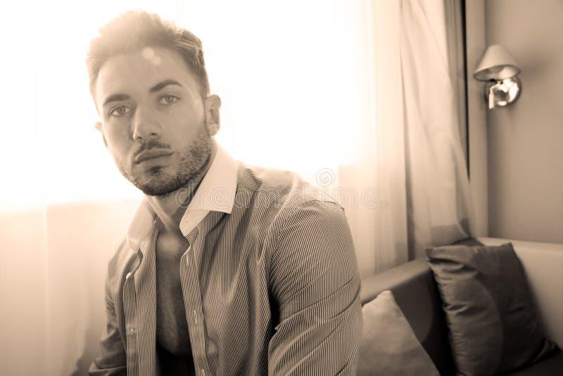 El lazo que lleva del hombre de negocios hermoso y la camisa abierta se sienta delante de la ventana de la habitación fotos de archivo