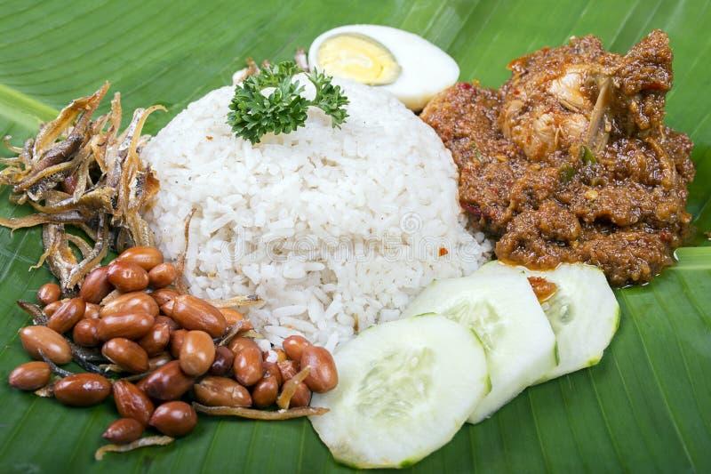 El lemak de Nasi, un plato tradicional del arroz de la goma del curry del malay sirvió en una hoja del plátano imagen de archivo