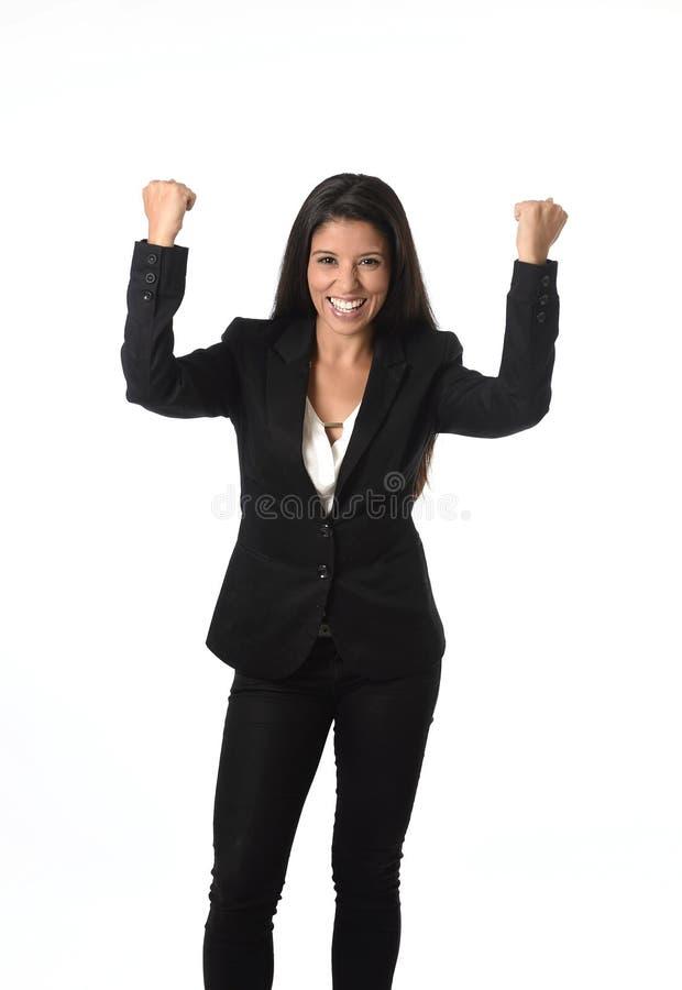 El levantamiento feliz sonriente del traje formal de la oficina de la empresaria que lleva latina arma en la victoria imagen de archivo libre de regalías