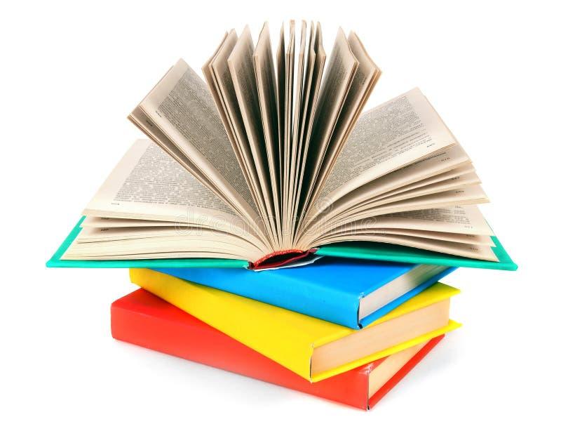El libro abierto en una pila de libros multicolores fotos de archivo
