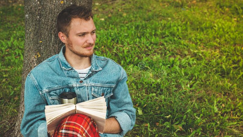 El libro de lectura sonriente del hombre joven al aire libre con una tela escocesa roja caliente y una taza de té el otoño del fo imagenes de archivo