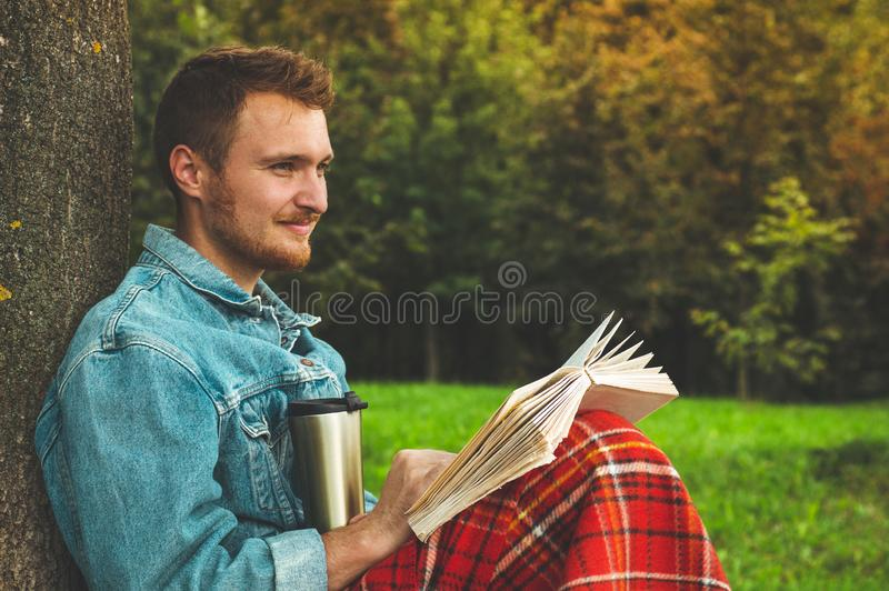 El libro de lectura sonriente del hombre joven al aire libre con una tela escocesa roja caliente y una taza de té el otoño del fo foto de archivo