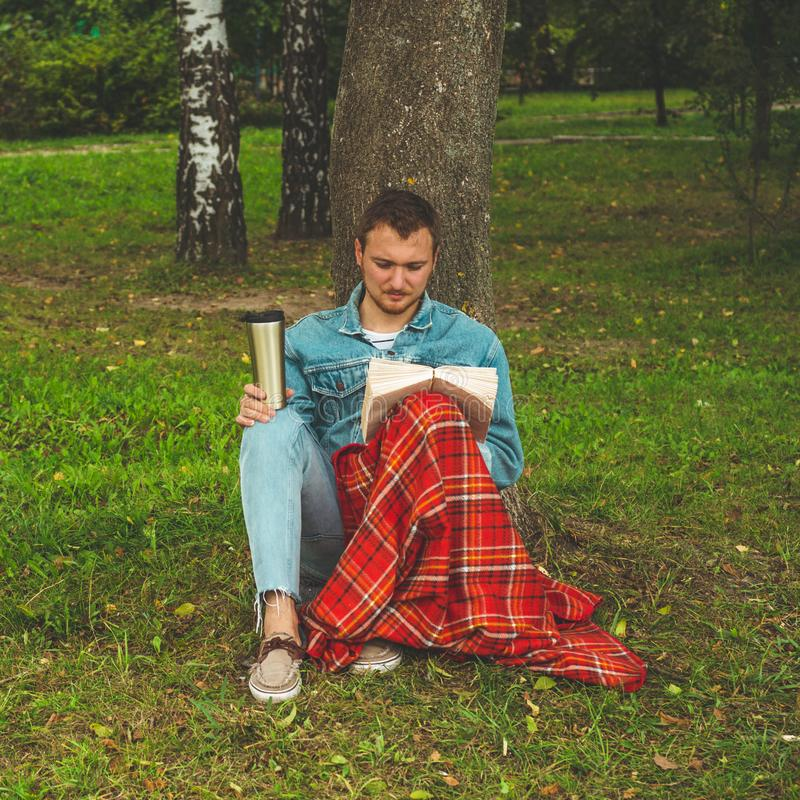 El libro de lectura sonriente del hombre joven al aire libre con una tela escocesa roja caliente y una taza de té el otoño del fo imagen de archivo