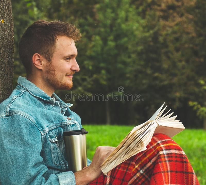 El libro de lectura sonriente del hombre joven al aire libre con una tela escocesa roja caliente y una taza de té el otoño del fo fotos de archivo