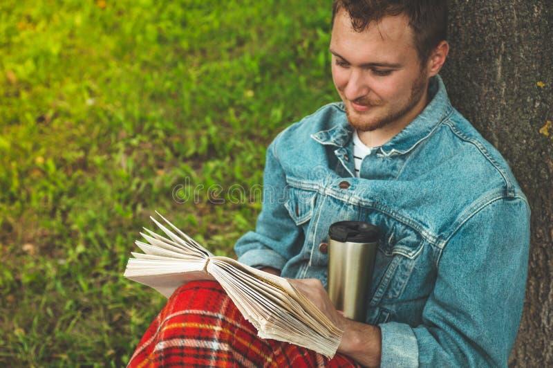 El libro de lectura sonriente del hombre joven al aire libre con una tela escocesa roja caliente y una taza de té el otoño del fo imagen de archivo libre de regalías