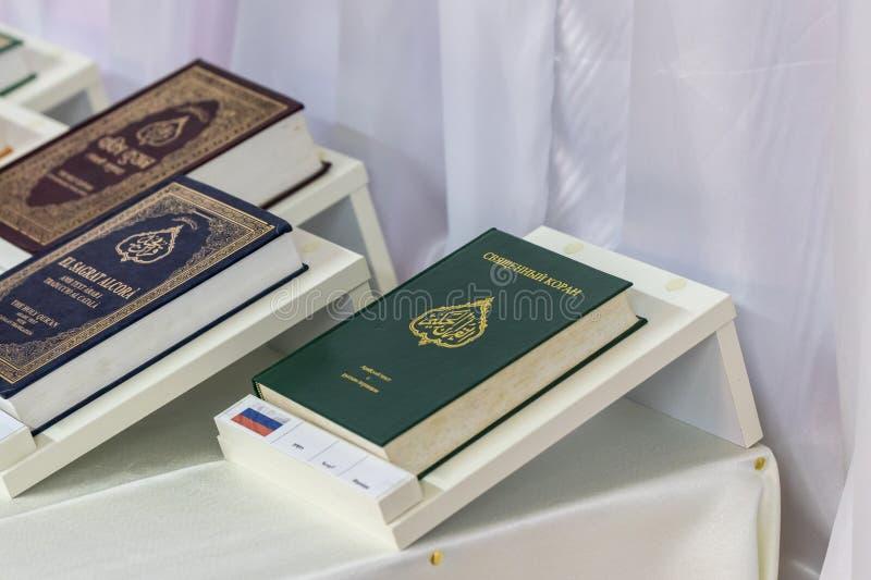 El libro santo del Quran en ruso está en la tabla al lado de los libros en otras idiomas en la mezquita de Ahmadiyya Shaykh Mahmu foto de archivo