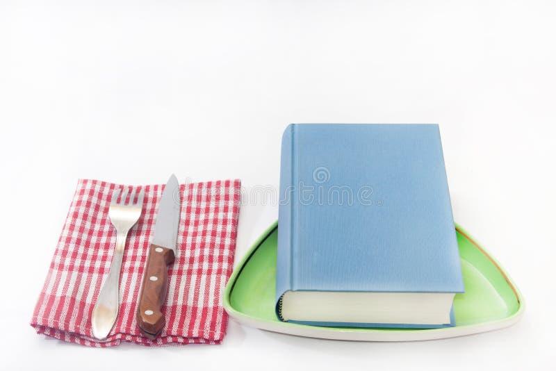 El libro sirvió en la placa con la bifurcación y el cuchillo imágenes de archivo libres de regalías