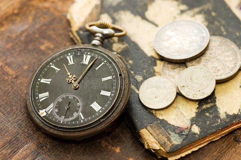 El libro viejo, el reloj viejo y el dinero fotografía de archivo libre de regalías