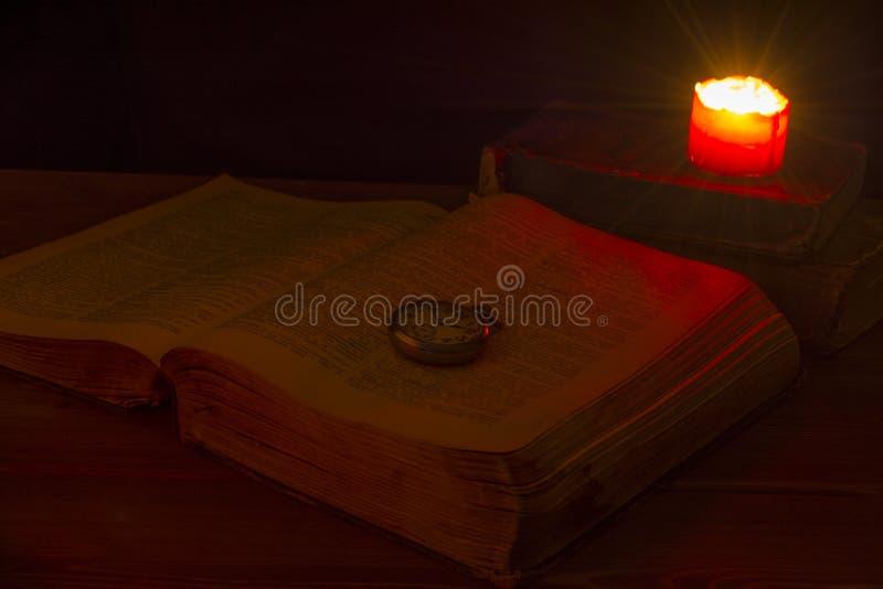 El libro viejo en la biblioteca por luz de una vela La biblia está en la tabla Reloj de bolsillo viejo Edades Medias divination p imagen de archivo
