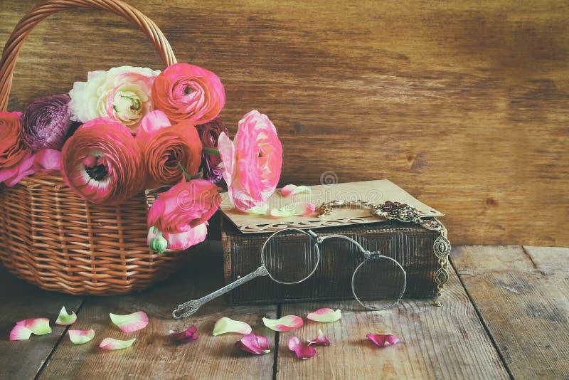 El libro viejo y los vidrios al lado del campo hermoso florece fotografía de archivo libre de regalías