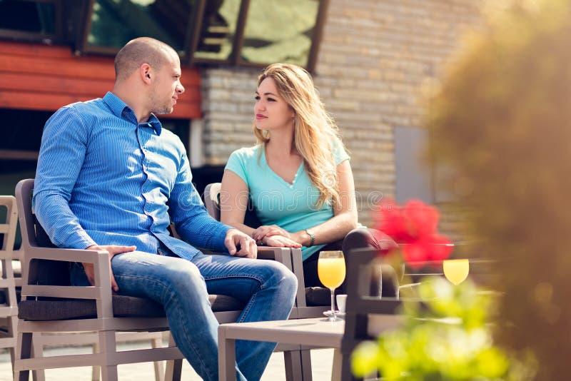 El ligar en un café Pares cariñosos hermosos que se sientan en un café que goza en café y la conversación Amor, romance, fechando imágenes de archivo libres de regalías