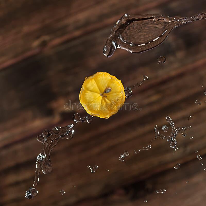 El limón con salpica en fondo marrón fotos de archivo libres de regalías