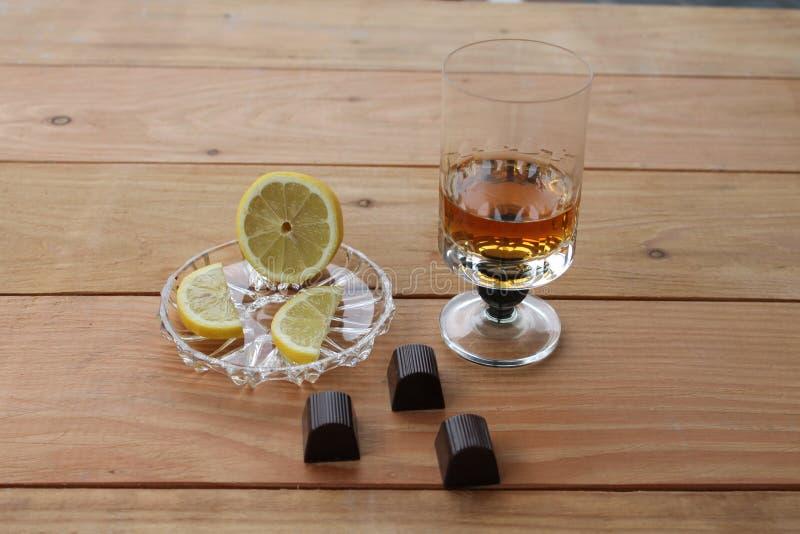 El limón del brandy del coñac corta el cubilete del brandy del limón del chocolate del whisky escocés en un fondo de madera con fotos de archivo libres de regalías