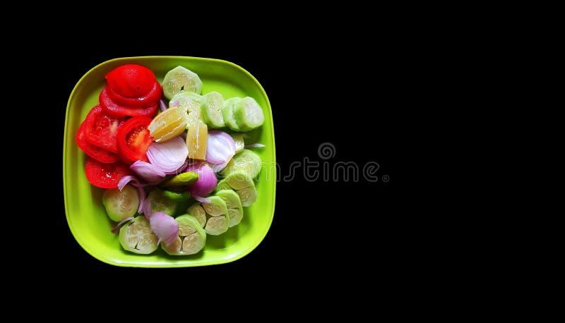 El limón del tomate del pepino de Oion cortó recientemente en una placa de la ensalada en fondo negro con el espacio para el text fotos de archivo