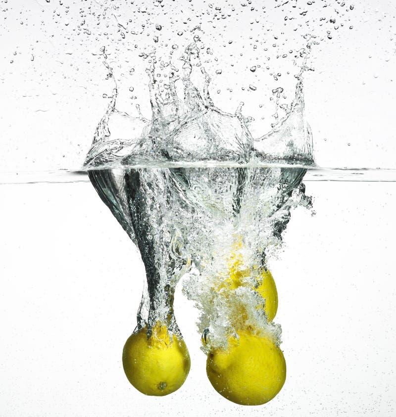 El limón fresco cayó en el agua fotografía de archivo libre de regalías