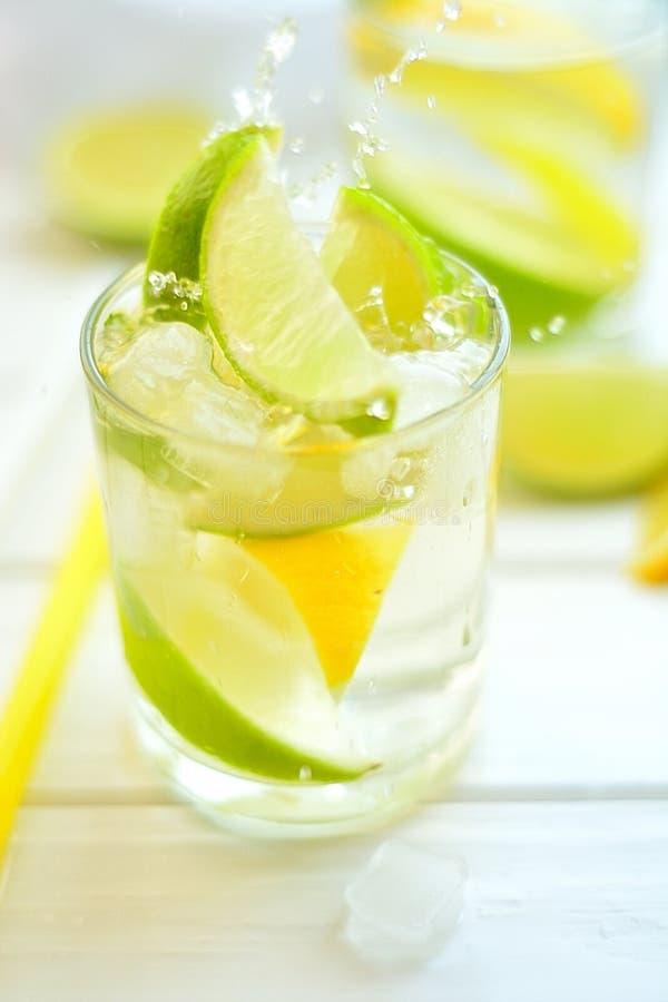 El limón y la cal del cóctel en un vidrio con agua salpica imagen de archivo
