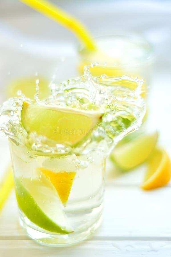 El limón y la cal del cóctel en un vidrio con agua salpica imagenes de archivo
