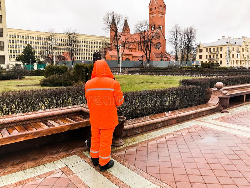 El limpiador de trabajo masculino en los guardapolvos anaranjados que llevan el trabajo de la ropa del traje limpia las calles de imagenes de archivo