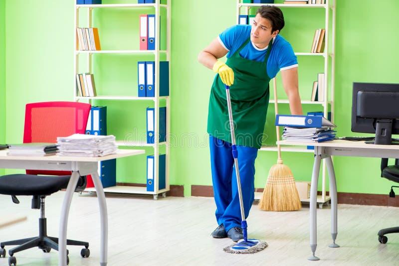El limpiador profesional hermoso masculino que hace aljofifar en la oficina imágenes de archivo libres de regalías
